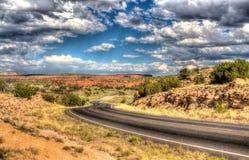 HDR Długa osamotniona droga po środku pustyni pod niebieskim niebem zdjęcia royalty free