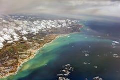 HDR flygbild av landskapet och kustlinjen med moln, snöig berg och sikten som hela vägen sträcker till horisonten Arkivbilder