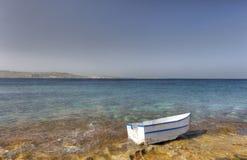 HDR-foto van een zonnige dag bij de overzeese kust met diep blauw schoon water en een aardig steenstrand en een kleine witte boot Royalty-vrije Stock Foto's