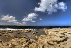 HDR-foto van een zonnige dag die bij de overzeese kust met diep blauw schoon water en een aardig steenstrand en vegetatie daar gr Royalty-vrije Stock Afbeeldingen