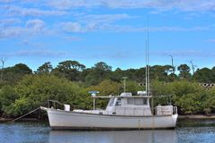 HDR Image of a Boat. This is an HDR image of a old rustic boat with blue cloudy skies Stock Image