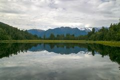 Natural calm water mirror of the cloudy sky, mountains, hills and forest, Lake Matheson in West Coast, Fox Glacier, New Zealand stock image