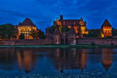HDR image of medieval castle in Malbork at night. With reflection in river Stock Photo
