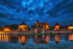 HDR image of medieval castle in Malbork at night. With reflection in river Stock Image