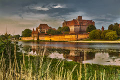 HDR image of medieval castle in Malbork at night with reflection. In river Royalty Free Stock Images
