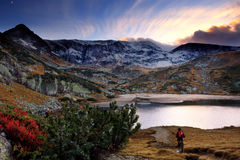 HDR mountain sunset. Beautiful HDR high mountain landscape with hiker near lake Royalty Free Stock Photography