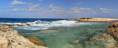 HDR panorama photo of a sunny day at the rocky sea coast with deep blue clean water and small rock formations Royalty Free Stock Photos