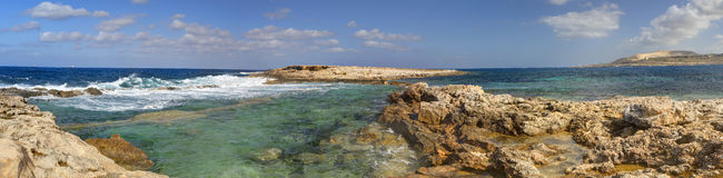 HDR panorama photo of a sunny day at the rocky sea coast with deep blue clean water and small rock formations Royalty Free Stock Photo
