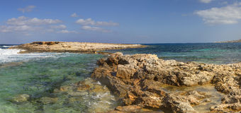 HDR panorama photo of a sunny day at the rocky sea coast with deep blue clean water and small rock formations Stock Images
