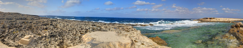 HDR panorama photo of a sunny day at the rocky sea coast with deep blue clean water and small rock formations Stock Photo