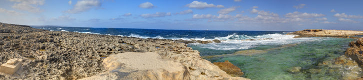 HDR panorama photo of a sunny day at the rocky sea coast with deep blue clean water and small rock formations Stock Photos