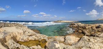 HDR panorama photo of a sunny day at the rocky sea coast with deep blue clean water and small rock formations Royalty Free Stock Image