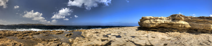 HDR panorama photo of a sunny day at the sea coast with deep blue clean water and a nice stone beach and a large rock on the right Royalty Free Stock Photo