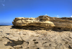 HDR panorama photo of a sunny day at the sea coast with deep blue clean water and a nice stone beach and a large rock on the right Royalty Free Stock Photography