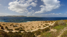 HDR panorama photo of a sunny day at the sea coast with deep blue clean water and a nice stone beach and vegetation growing there Stock Images