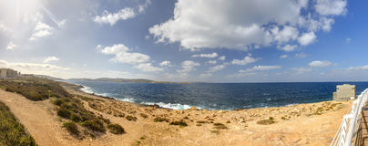 HDR panorama photo of a sunny day at the sea coast with deep blue clean water and a nice stone beach and vegetation growing there Stock Photography