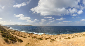 HDR panorama photo of a sunny day at the sea coast with deep blue clean water and a nice stone beach and vegetation growing there Stock Photos