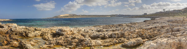 HDR panorama photo of a sunny day at the sea coast with deep blue clean water and a nice stone beach and vegetation growing there Stock Photo