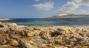 HDR panorama photo of a sunny day at the sea coast with deep blue clean water and a nice stone beach and vegetation growing there Royalty Free Stock Photography