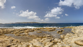 HDR panorama photo of a sunny day at the sea coast with deep blue clean water and a nice stone beach and vegetation growing there Royalty Free Stock Photos