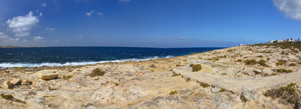 HDR panorama photo of a sunny day at the sea coast with deep blue clean water and a nice stone beach and vegetation growing there Royalty Free Stock Image