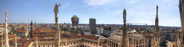 HDR panorama photo of white marble statues of Cathedral Duomo di Milano on piazza, Milan cityscape and the Royal Palace of Milan Royalty Free Stock Photo