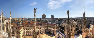 HDR panorama photo of white marble statues of Cathedral Duomo di Milano on piazza, Milan cityscape and the Royal Palace of Milan Stock Photos