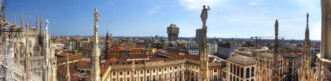 HDR panorama photo of white marble statues of Cathedral Duomo di Milano on piazza, Milan cityscape and the Royal Palace of Milan Royalty Free Stock Photos
