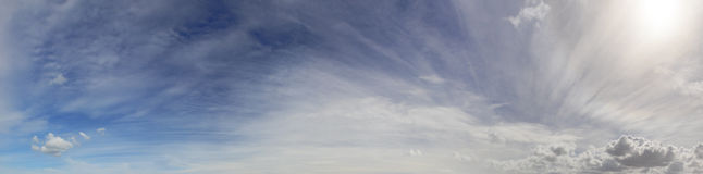 HDR panorama view of the blue sky with long streaks of clouds and a sun on the right Royalty Free Stock Photography