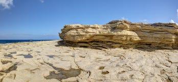 HDR-panoramafoto van een zonnige dag bij de overzeese kust met diep blauw schoon water en een aardig steenstrand en een grote rot Stock Foto's