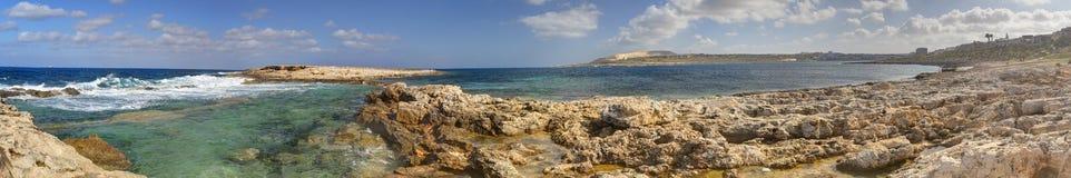 HDR panoramafotoet av en solig dag på den steniga havskusten med djupblått rent vatten och små vaggar bildande arkivfoton