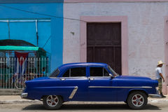 HDR parked blue american classic car in Cuba with a latino Royalty Free Stock Images