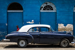 HDR parked blue american classic car in front side from a old building in Cuba with a latino Stock Photos