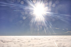 HDR photo of an airplane wing against the blue sky with a cloud cover underneath and brigh shining sun in in front of it Stock Photo