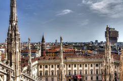 HDR photo of the marble statues and decorations on the Cathedral Duomo di Milano on piazza in Milan and Royal Palace of Milan Stock Image