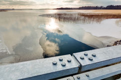 HDR photo of melt water behind metallic bridge railings at a freezing lake Stock Image