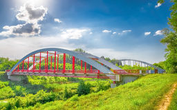 Hdr photo of a red bridge over the river and a railway bridge in the background Stock Photography