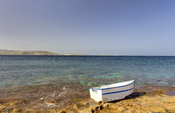 HDR photo of a sunny day at the sea coast with deep blue clean water and a nice stone beach and a small white boat in front Stock Photo