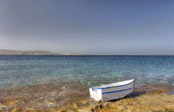 HDR photo of a sunny day at the sea coast with deep blue clean water and a nice stone beach and a small white boat in front Royalty Free Stock Photos