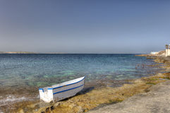 HDR photo of a sunny day at the sea coast with deep blue clean water and a nice stone beach and a small white boat in front Royalty Free Stock Image
