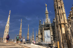 HDR photo of he white marble statues and decorations on the Cathedral Duomo di Milano on piazza in Milan with visitors Royalty Free Stock Image