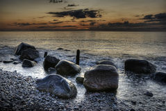 HDR stones in the ocean with sunrise Stock Image