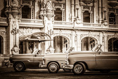HDR - Street life with parked american convertible vintage cars before the gran teatro in Havana Cub. A - Retro Serie SEPIA Cuba Reportage Royalty Free Stock Images