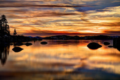 HDR Tahoe Sunset. Sunset at Sand Harbor, Lake Tahoe, Nevada.  Large granite boulders reflecting into glassy water with warm light Stock Image