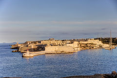 HDR view on the historic buildings of the Valletta city, Malta capital, with an old red and white lighthouse. View on the historic buildings of the Valletta city Royalty Free Stock Photography