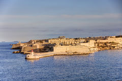 HDR view on the historic buildings of the Valletta city, Malta capital, with an old red and white lighthouse Royalty Free Stock Photos