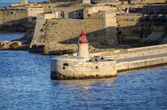 HDR view on the historic buildings of the Valletta city, Malta capital, with an old red and white lighthouse Stock Images