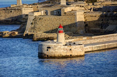 HDR view on the historic buildings of the Valletta city, Malta capital, with an old red and white lighthouse Stock Photography