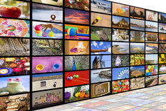 HDTV broadcast concept. Big TV videowall with different channels in a white room with reflection stock image