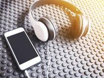 Hełmofon i telefon komórkowy na czarnej gumie matujemy tło Zdjęcie Royalty Free
